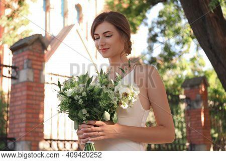 Gorgeous Bride In Beautiful Wedding Dress With Bouquet Near Church