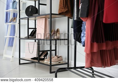 Different Stylish Shoes And Bags On Shelving Unit In Dressing Room