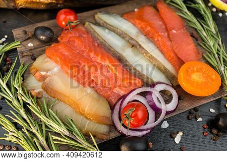Sliced Fish Salmon, Trout, Halibut With Vegetables And Rosemary, On A Black Wooden Background