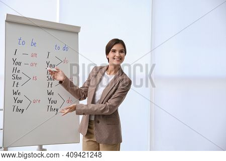 English Teacher Near Whiteboard In Class At Lesson. Space For Text
