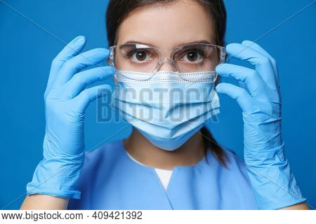 Doctor In Protective Mask, Medical Gloves And Glasses Against Blue Background