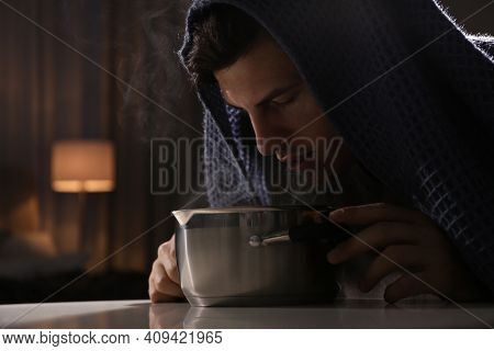 Man With Plaid Doing Inhalation Above Saucepot At Table Indoors