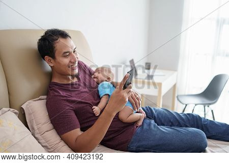 Father Holding His Newborn Sweet Adorable Baby Sleeping On His Arms While Using Mobile Phone On The