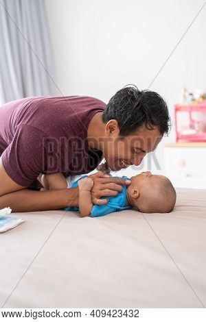 Asian Father Changing His Infant Baby Diaper