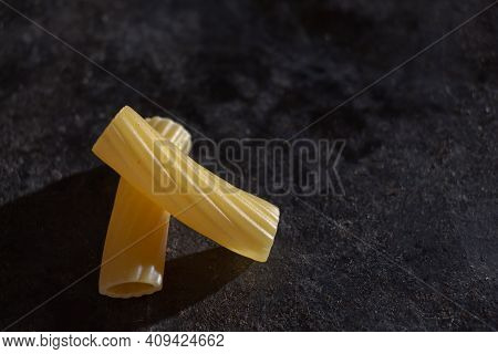 Uncooked Italian Rigatoni Pasta In Yellow On A Dark Background With A Copyspace