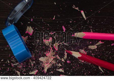 Pencil Sharpener On A Dark Wooden Background. A Broken And Sharpened Pencil.