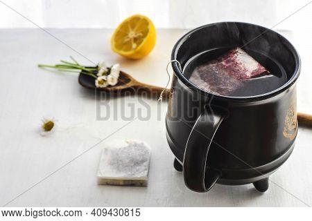 Chamomile Flowers And Chamomile Tea In Black Big Coffee Cup/  Chamomile Tea In Cup With Flowers And