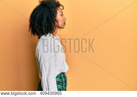 Beautiful african american woman with afro hair wearing scholar skirt looking to side, relax profile pose with natural face with confident smile.