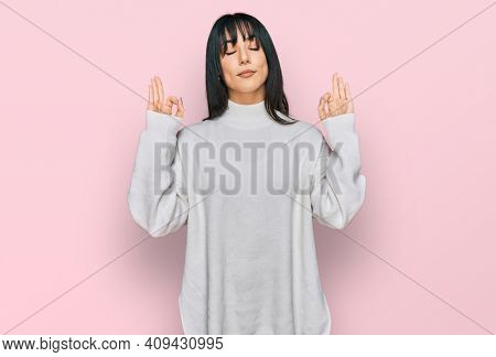 Young brunette woman with bangs wearing casual turtleneck sweater relax and smiling with eyes closed doing meditation gesture with fingers. yoga concept.