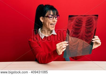 Young brunette woman with bangs holding chest radiography celebrating crazy and amazed for success with open eyes screaming excited.