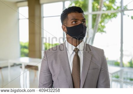 Portrait Of African Businessman With Surgical Medical Mask For Protection Thinking At Office
