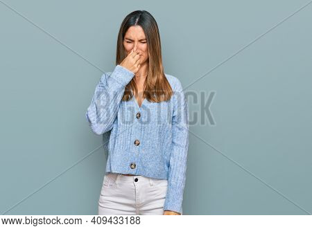 Young woman wearing casual clothes smelling something stinky and disgusting, intolerable smell, holding breath with fingers on nose. bad smell