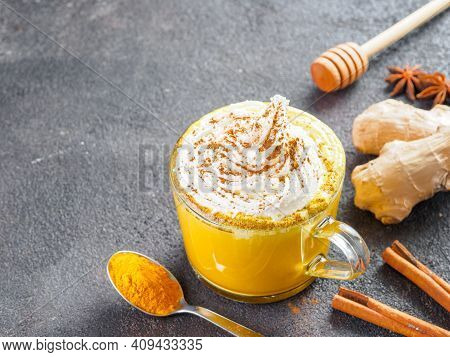 Healthy Drink Golden Turmeric Latte With Whipped Cream In Glass Cup. Gold Milk, Ginger Root, Cinnamo