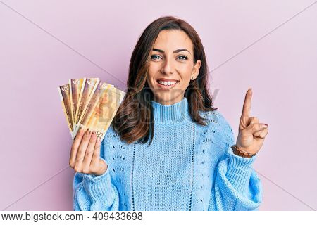 Young brunette woman holding 500 norwegian krone banknotes smiling with an idea or question pointing finger with happy face, number one