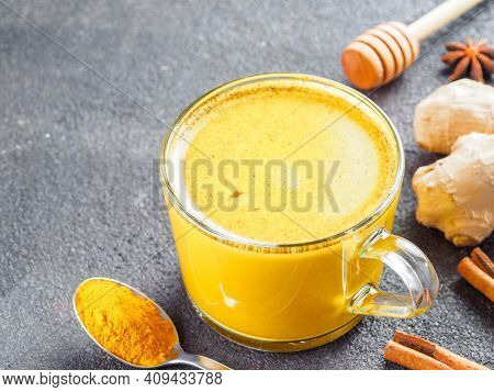 Healthy Drink Golden Turmeric Latte In Glass Cup.gold Milk With Turmeric, Ginger Root, Cinnamon Stic