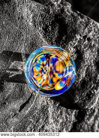Overhead Shot Of Crystal Ball On Stone. The Focus Is On The Crystal Ball.