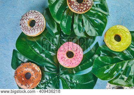 Multicolored Donuts With Frosting, Sprinkles Lie On Monstera Leaves On Blue Background.