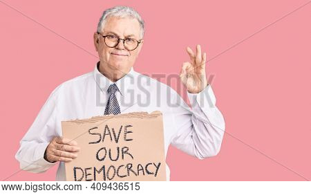 Senior grey-haired man wearing business clothes holding save our democracy protest banner doing ok sign with fingers, smiling friendly gesturing excellent symbol