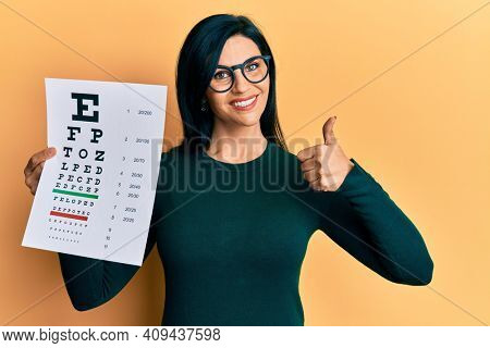 Young caucasian woman holding optometry glasses and eyesight test smiling happy and positive, thumb up doing excellent and approval sign