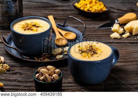 Corn Soup, Vegan Cuisine. Traditional Autumn Corn Soup. Served With Corn Cobs, Roasted Pistachios An
