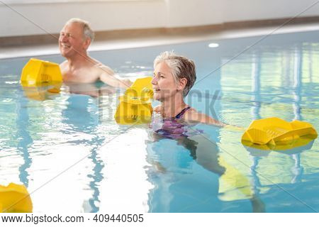 Senior women and men in Rehabilitation training in a water gymnastics class