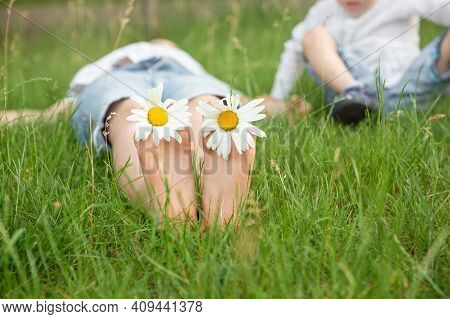 Boy Lying On Green Grass Outdoors In Park. Happy Summer Feet. Child With Daisy Lying In Sunny Meadow