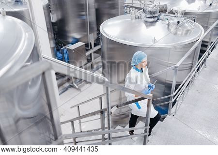Worker Female Operator In Uniform Holding Computer Tablet Checking Food Factory Production Line And