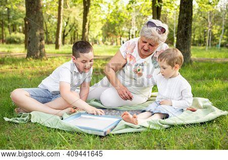 Happy Moments With Grandmother Outdoors. Grandmother Playing With Her Grandchildren At Nature. Cheer