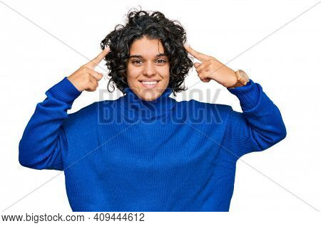 Young hispanic woman with curly hair wearing turtleneck sweater smiling pointing to head with both hands finger, great idea or thought, good memory