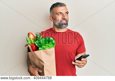 Middle age handsome man holding bag of groceries using smartphone smiling looking to the side and staring away thinking.