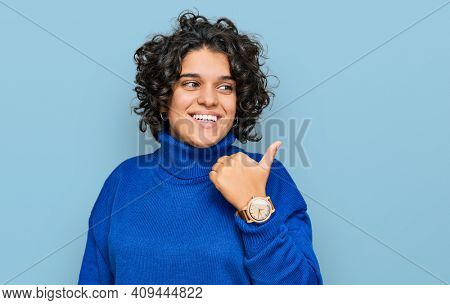 Young hispanic woman with curly hair wearing turtleneck sweater smiling with happy face looking and pointing to the side with thumb up.
