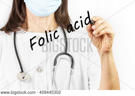 Doctor With Mask Writing The Word Folic Acid On A White Background. Health Concept
