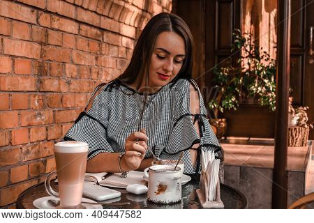 Young Business Woman Sitting In Cafe Drinking Coffee. Beautiful Girl Is Working Against An Orange Br
