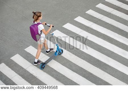 Schoolgirl Carrying Scooter And Crossing Road On Way To School. Zebra Traffic Walk Way In The City.