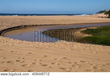 Blue River With Sandy Banks Meandering Into The Sea