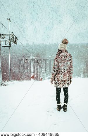 Woman In Winter Coat Standing On Slope Near Loop-line Ski Lift During Snowfall. Beautiful Winter Vie