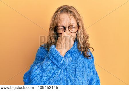 Middle age blonde woman wearing glasses and casual winter sweater smelling something stinky and disgusting, intolerable smell, holding breath with fingers on nose. bad smell