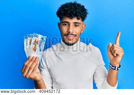 Young arab handsome man holding 100 swiss franc banknotes smiling with an idea or question pointing finger with happy face, number one