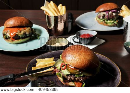 Different Burgers On The Table, Served Frenc Fries And Sauces On Plates. The Closest Spicy Beef Burg