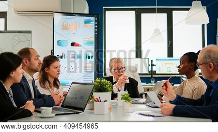Group Of Diverse Business People Discussing With Partners On Video Call During Video Meeting Sitting