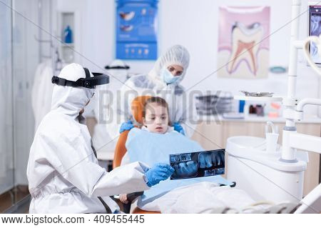 Dentist Dressed In Ppe Suit Reviewing Panoramic Mouth Radiography Of Little Girl Patient. Stomatolog