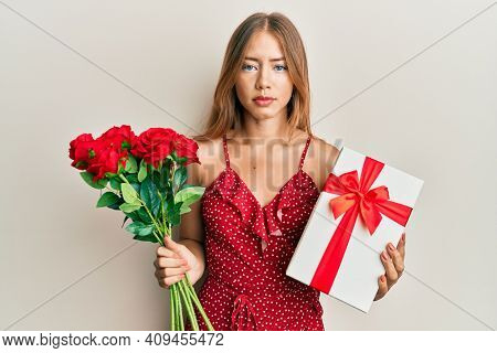 Beautiful young blonde woman holding anniversary present and bouquet of flowers relaxed with serious expression on face. simple and natural looking at the camera.