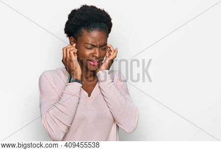 Young african american girl wearing casual clothes covering ears with fingers with annoyed expression for the noise of loud music. deaf concept.