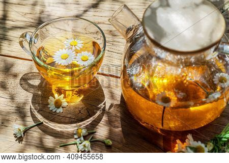Herbal chamomile tea and chamomile flowers near teapot and tea glass. Top view.