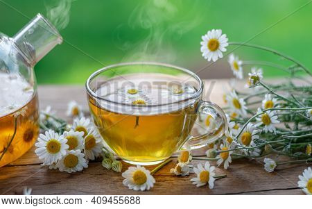 Glass of herbal chamomile tea and chamomile flowers on old wooden table. Close-up.