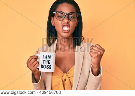 Young african american woman drinking mug of coffe with i am the boss message annoyed and frustrated shouting with anger, yelling crazy with anger and hand raised