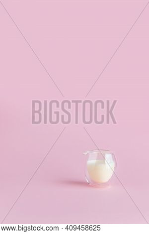 Milk In A Glass On A Pink Background. Vertical Photo