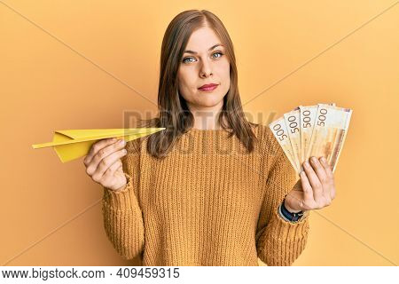 Beautiful caucasian woman holding paper airplane and 500 norwegian krone relaxed with serious expression on face. simple and natural looking at the camera.