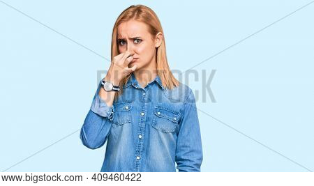 Beautiful caucasian woman wearing casual denim jacket smelling something stinky and disgusting, intolerable smell, holding breath with fingers on nose. bad smell