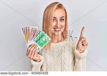 Beautiful caucasian woman holding norwegian krone banknotes smiling with an idea or question pointing finger with happy face, number one